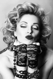 Retro stijl zwart-wit portret van sexy volwassen speelse vrouw die een kus blaast