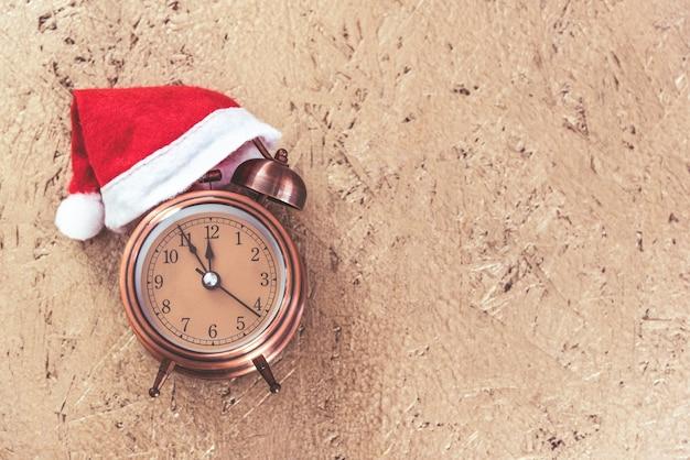 Retro-stijlwekker met rode kerstman hoed op gouden houten textuur met copyspace