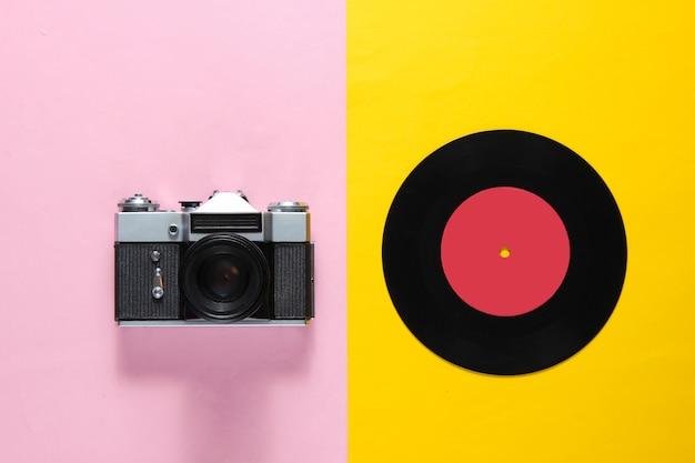 Retro stilleven, jaren 70. vinylplaat en filmcamera op roze geel. bovenaanzicht. plat leggen
