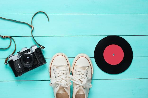 Retro stilleven. ouderwetse sneakers, vinylplaat en vintage filmcamera op blauw hout. bovenaanzicht. plat leggen