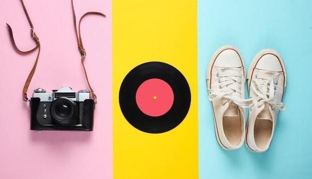 Retro stilleven. ouderwetse sneakers, vinylplaat, vintage filmcamera. bovenaanzicht. popart plat leggen