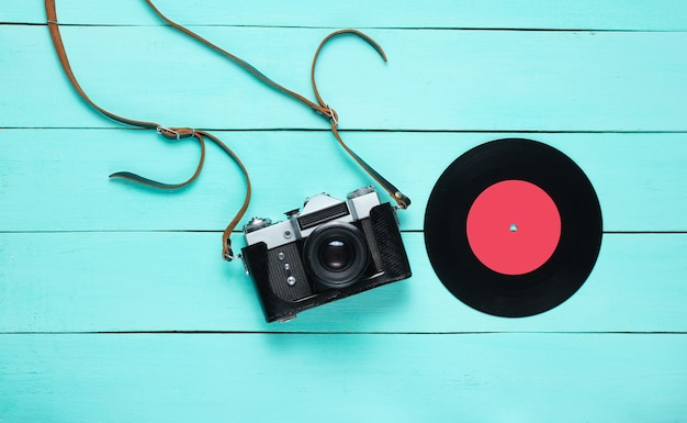 Retro stilleven. vinylplaat en filmcamera op blauw hout. bovenaanzicht. plat leggen