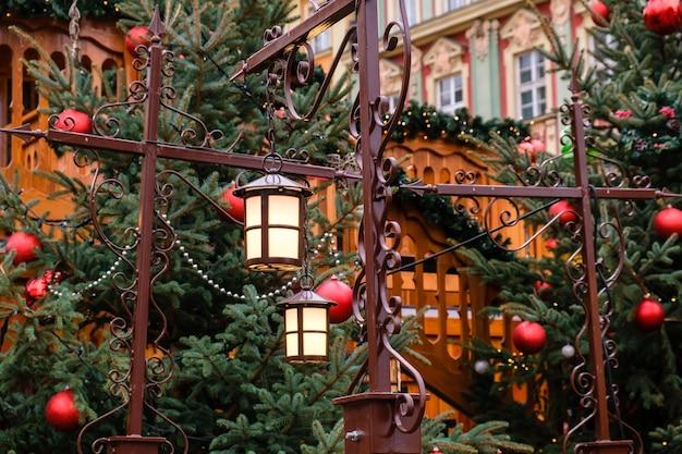 Retro straatlantaarns en rode kerstballen met led-slingers op versierde natuurlijke nieuwjaarsbomen op een feestelijke kerstmarkt in de centrale stadsstraat.