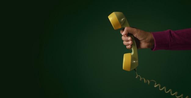 Retro telefoon. hand met een handset. communicatieconcept.