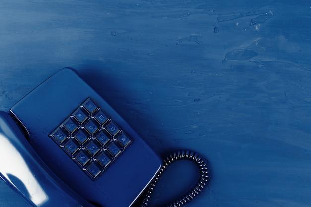 Retro telefoon van blauwe kleur op klassieke blauwe oppervlak