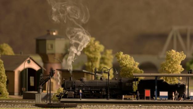 Retro treinstation met lokomotief en mensen.