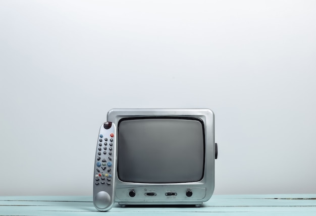 Retro tv-ontvanger met tv-afstandsbediening op witte muur