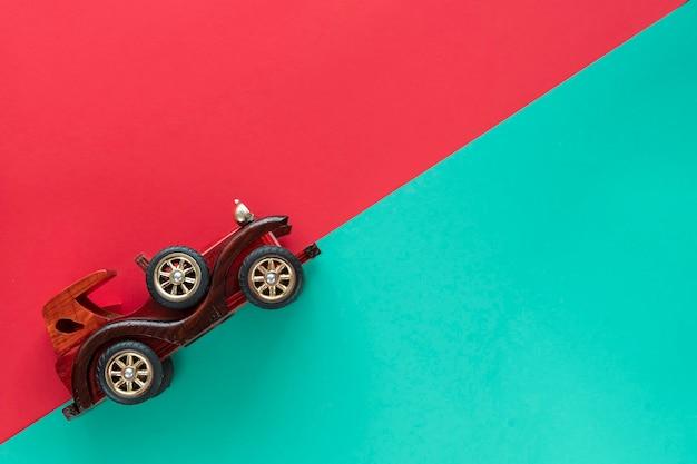Retro vintage auto op veelkleurige papier achtergrond. vakantie, levering, reisconcept. bovenaanzicht, platliggend. rode muntstelen.