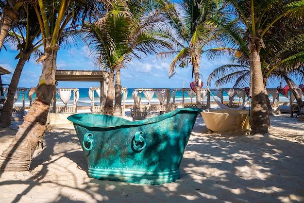 Retro vintage stijl metalen badkuip op zand in een prachtig strandresort