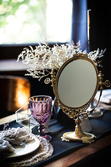 Retro vintage tafel. regeling op tafel, antieke spiegel, borden, vintage mok. oude spiegel op tafel