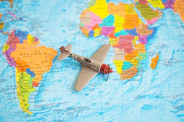 Retro vliegtuig op kleurrijke wereldkaart, plaats voor handtekening