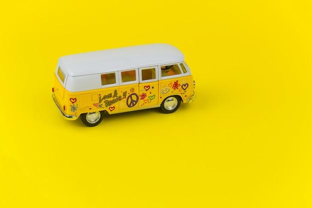 Retro volkswagenbusstuk speelgoed dat over geel wordt geïsoleerd
