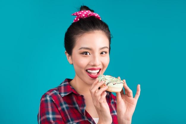 Retro vrolijke vrouw geniet van snoep, dessert staande over blauwe achtergrond.