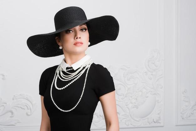 Retro vrouw portret. vintage stijl meisje met ouderwetse hoed, kapsel en make-up