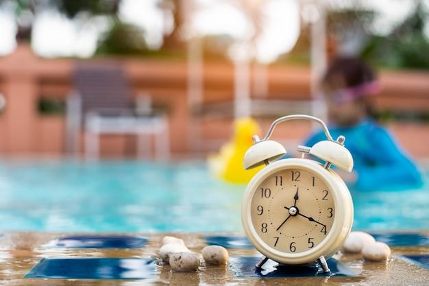 Retro wekker bij het zwembad met kinderen die zwembril dragen.