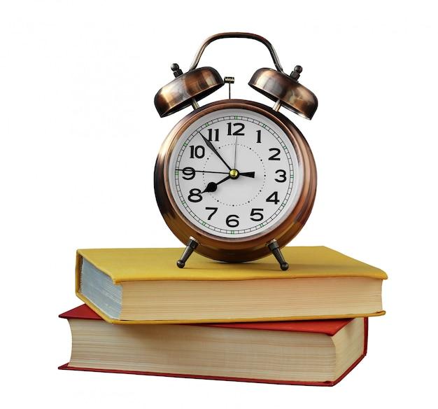 Retro wekker en boeken die op wit worden geïsoleerd.