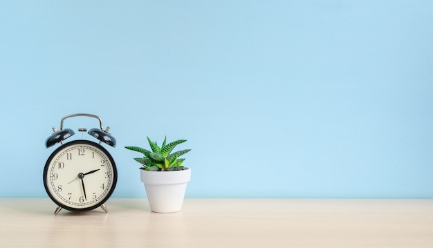 Retro wekker en huisplant in witte pot op een houten bureau op een blauwe muurachtergrond.