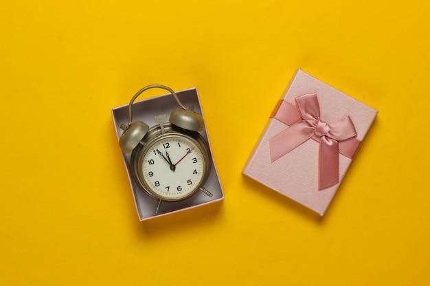 Retro wekker in geschenkdoos met strik op gele achtergrond. 11:55 uur. nieuwjaar, kerst concept. bovenaanzicht