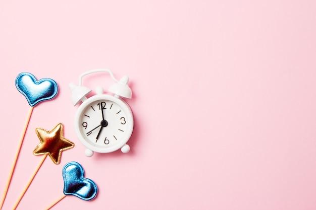 Retro wekker met partijdecoratie op roze achtergrond