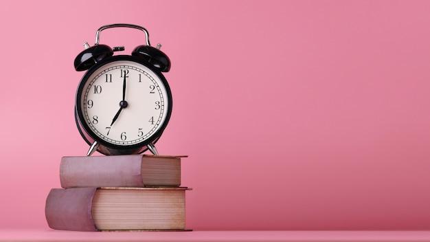Retro wekker met vintage boeken op roze houten bureau