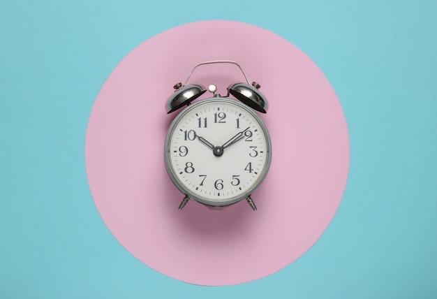 Retro wekker op blauwe achtergrond met roze pastel cirkel. bovenaanzicht