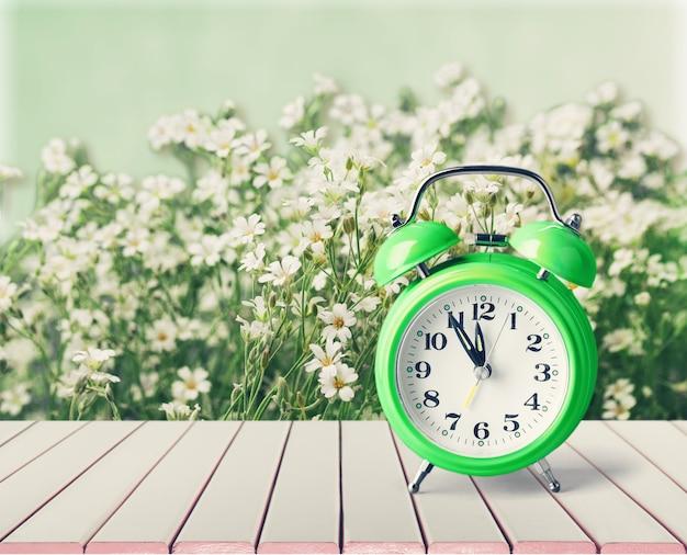 Retro wekker op bloemenachtergrond