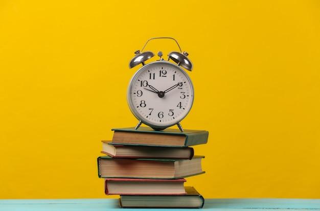 Retro wekker op een stapel boeken. geel