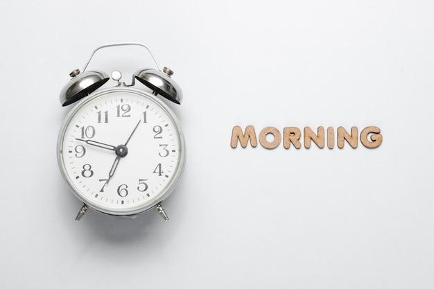 Retro wekker op grijze ondergrond met tekst ochtend met letters minimalistic concept