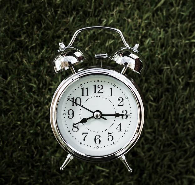 Retro wekker op groen gras. tijd concept