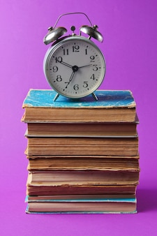 Retro wekker op stapel oude boeken op paarse tafel.