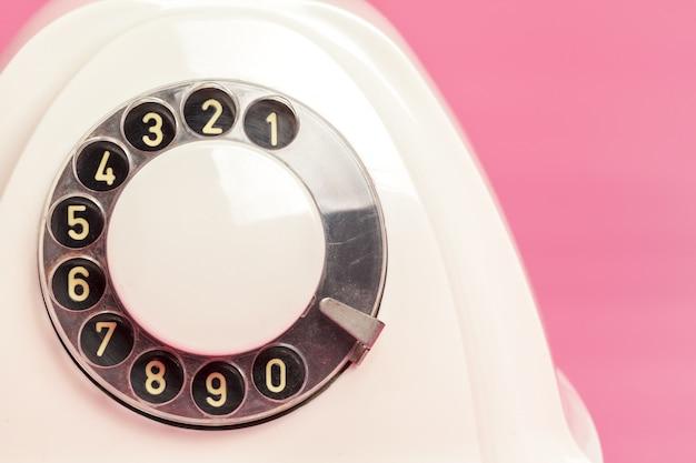 Retro witte telefoon op roze achtergrond