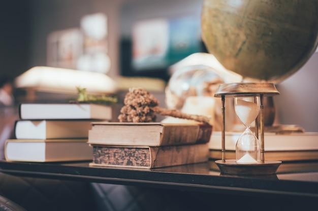 Retro zandloper, vervagen stapel van oude boeken