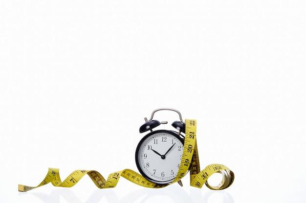 Retro zwarte wekker met geel meetlint op witte achtergrond succes concept