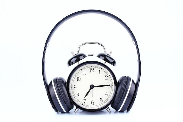 Retro zwarte wekker met hoofdtelefoon die op witte achtergrond wordt geïsoleerd.