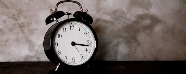 Retro zwarte wekker op een betonnen muur, selectieve aandacht, kopieer ruimte