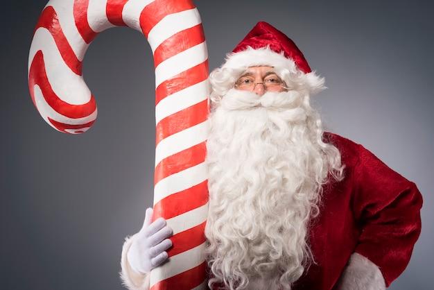 Reusachtig suikergoedriet dat door de kerstman wordt vastgehouden