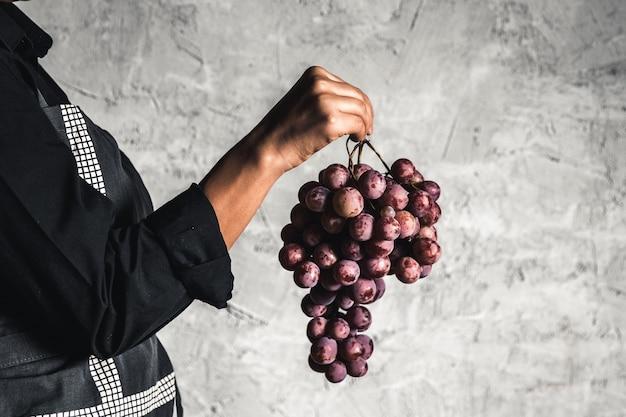 Reusachtige druiven bij de hand op een grijze achtergrond