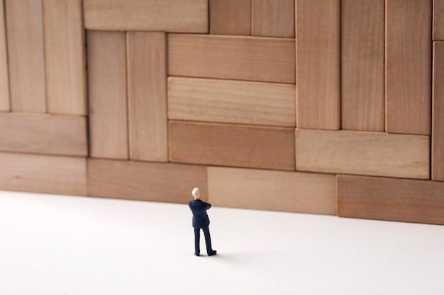 Reusachtige muur en miniatuurzakenman