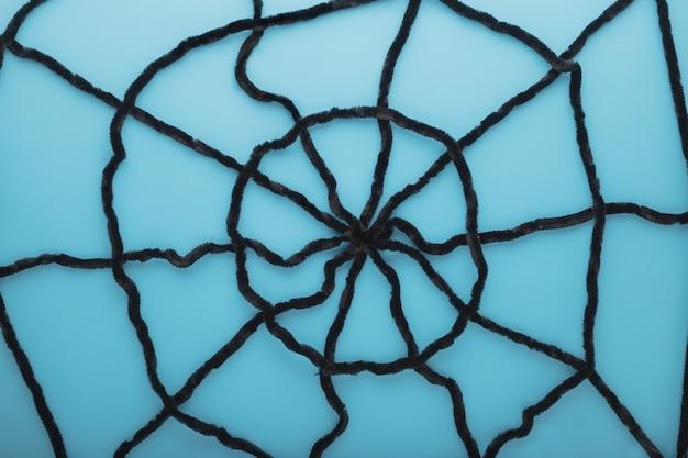 Reuze spinnenweb op een blauwe achtergrond. halloween decoraties concept. plat lag, bovenaanzicht, kopieer ruimte.