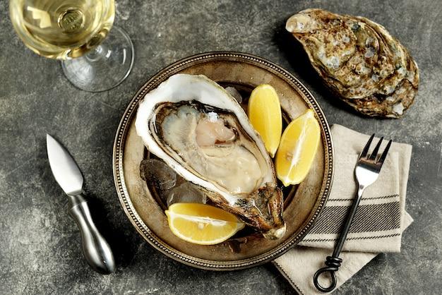 Reuze verse ongekookte oesters in een schelp met citroen op ijs. gezond eten. bovenaanzicht.