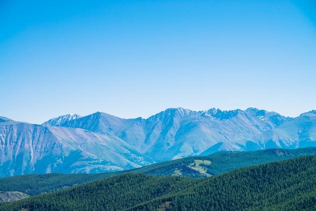 Reuzengebergte en gletsjers boven heuvels met bos. besneeuwde rand onder blauwe heldere hemel. sneeuwtop in hooglanden.