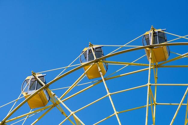 Reuzenrad met gele hutten. vreugde entertainment in stadspark.