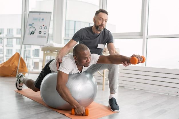 Revalidatie-oefeningen. leuke prettige hardwerkende man liggend op de medball tijdens een training