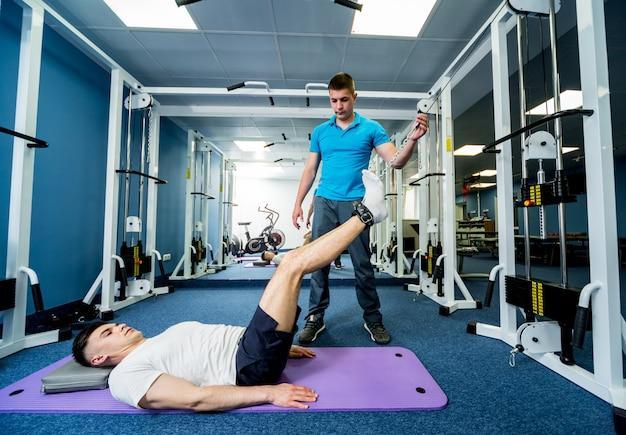 Revalidatietherapie. jonge man doen oefeningen op mat onder toezicht van fysiotherapeut.