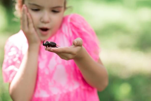 Rhinoceros beetle kruipen op de vingers van de menselijke hand.