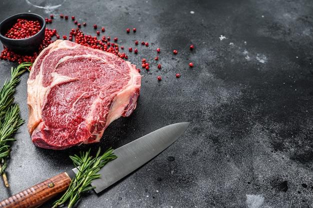 Ribeye on the bone of cowboy steak op raw marble beef op zwarte tafel.