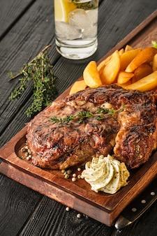 Ribeye steak met aardappelen, uien en gebakken cherrytomaatjes. sappige biefstuk met gearomatiseerde boter
