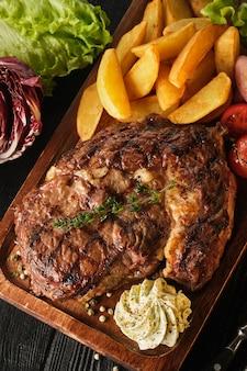 Ribeye steak met aardappelen, uien en gebakken cherrytomaatjes