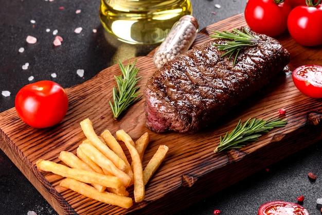 Ribeye steak met aardappelen, uien en kerstomaatjes. sappige biefstuk met gearomatiseerde boter