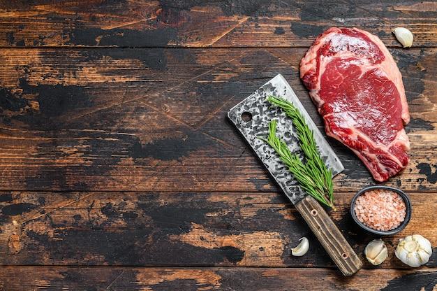 Ribeye steak op een hakmes. raw marble beef black angus, rib eye. donkere houten achtergrond. bovenaanzicht. kopieer ruimte.